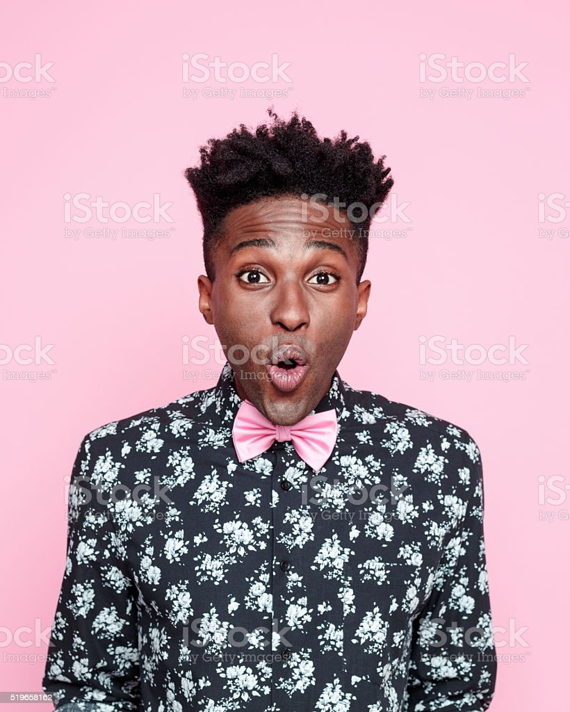 Surprised afro american guy against pink background stock photo