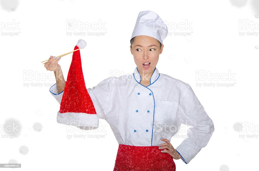 Surprised asian chef in christmas cap with chopsticks under snow stock photo