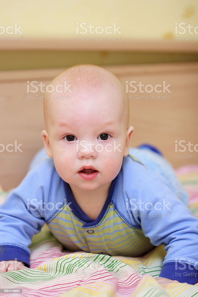 Surprised baby on bed stock photo
