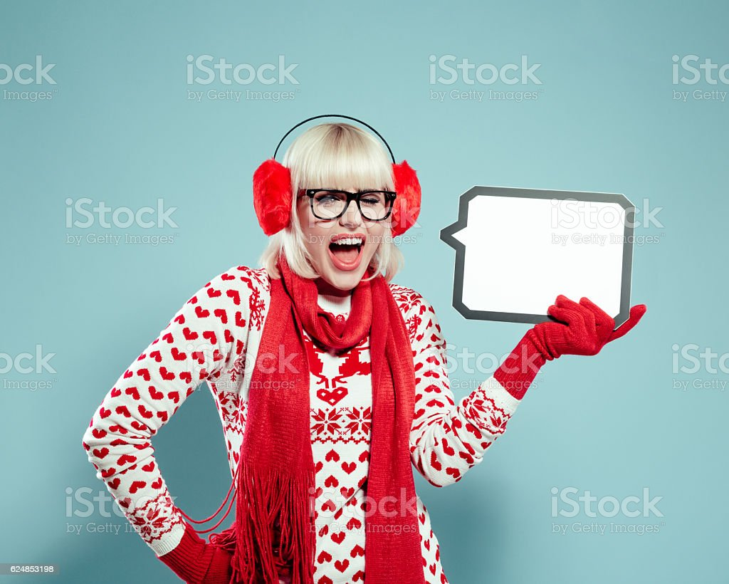 Surprised blonde young woman in winter outfit holding speech bubble stock photo