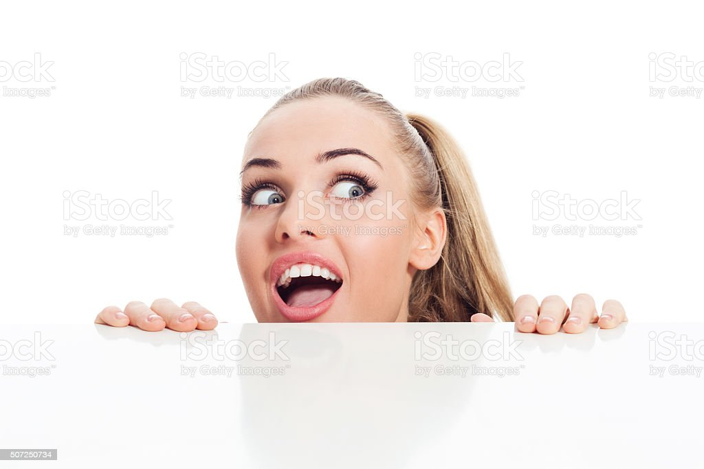 Surprised blonde young woman looking over table stock photo