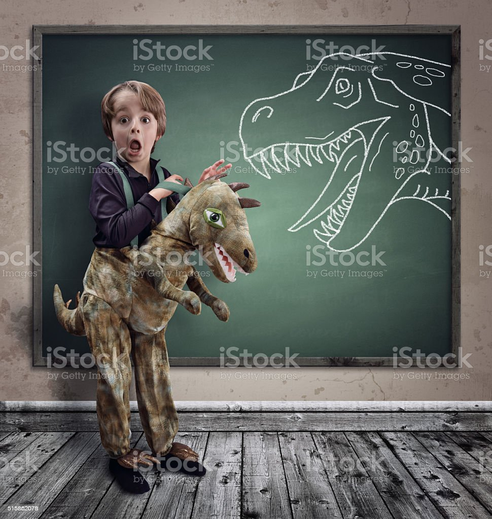 Surprised boy dressed in fancy dress as a dinosaur stock photo