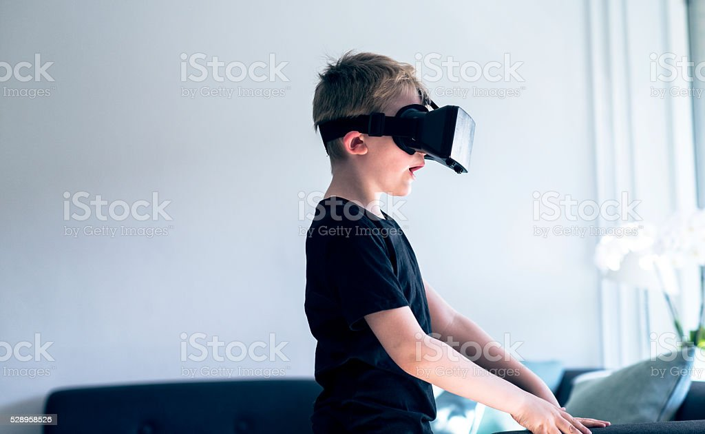 Surprised boy looks into a pair of VR glasses stock photo