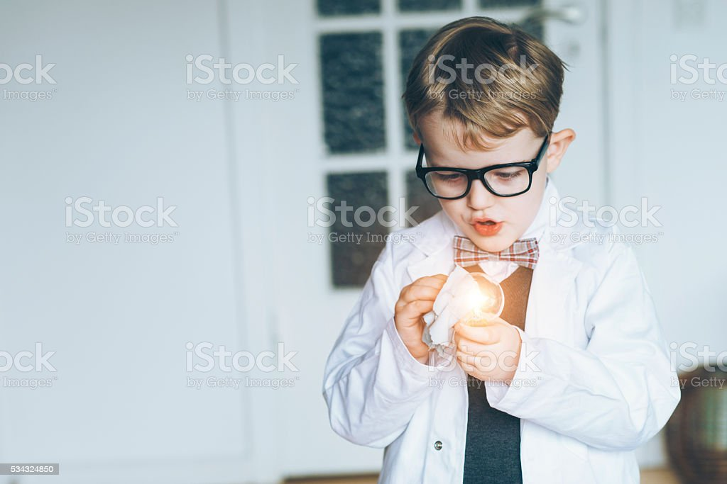 Surprised boy with lab coat makes light bulb invention stock photo