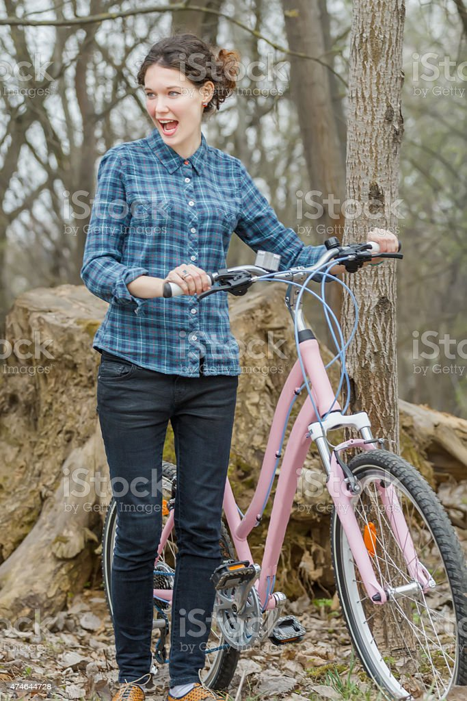 Surprised brunette girl walking and holding vintage pink bicycle stock photo