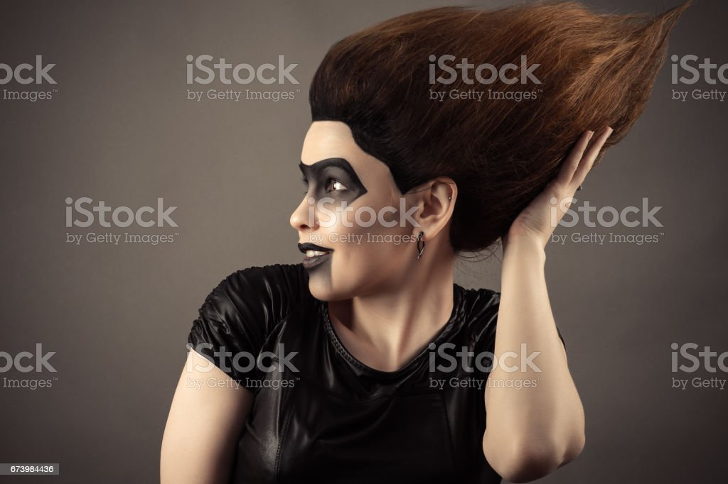 surprised brunette woman touching lush hair on head stock photo