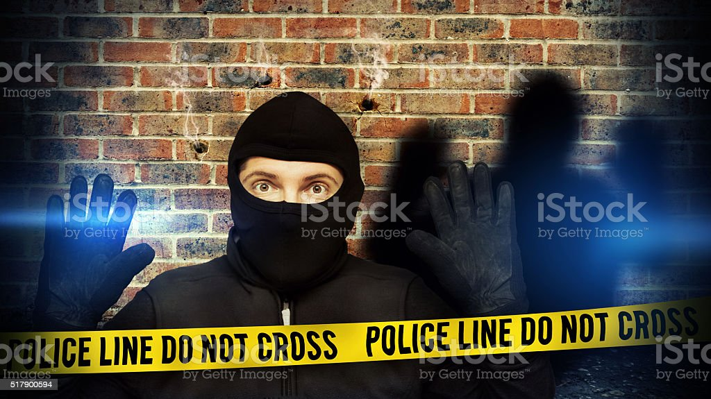 Surprised burglar stopped because of blue police light and take stock photo