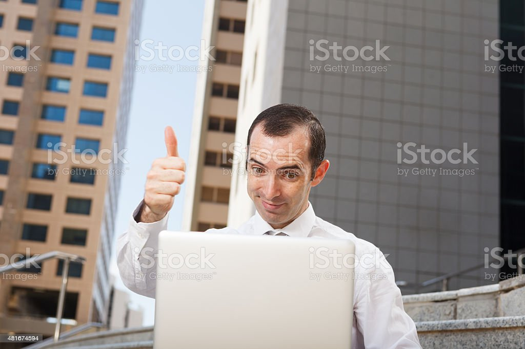 surprised business man sitting on steps with lthumb up stock photo