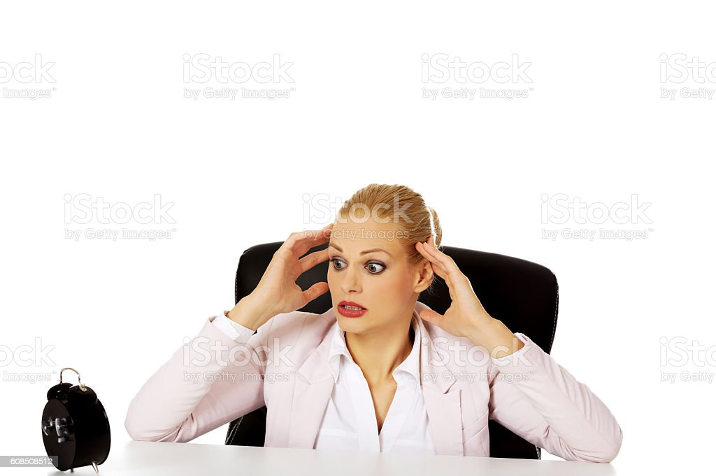 Surprised business woman looking at alarm clock behind the desk stock photo