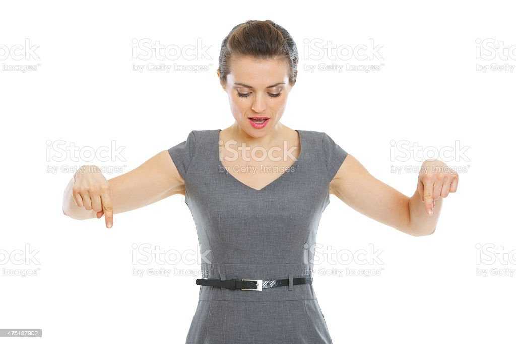 surprised business woman pointing down stock photo