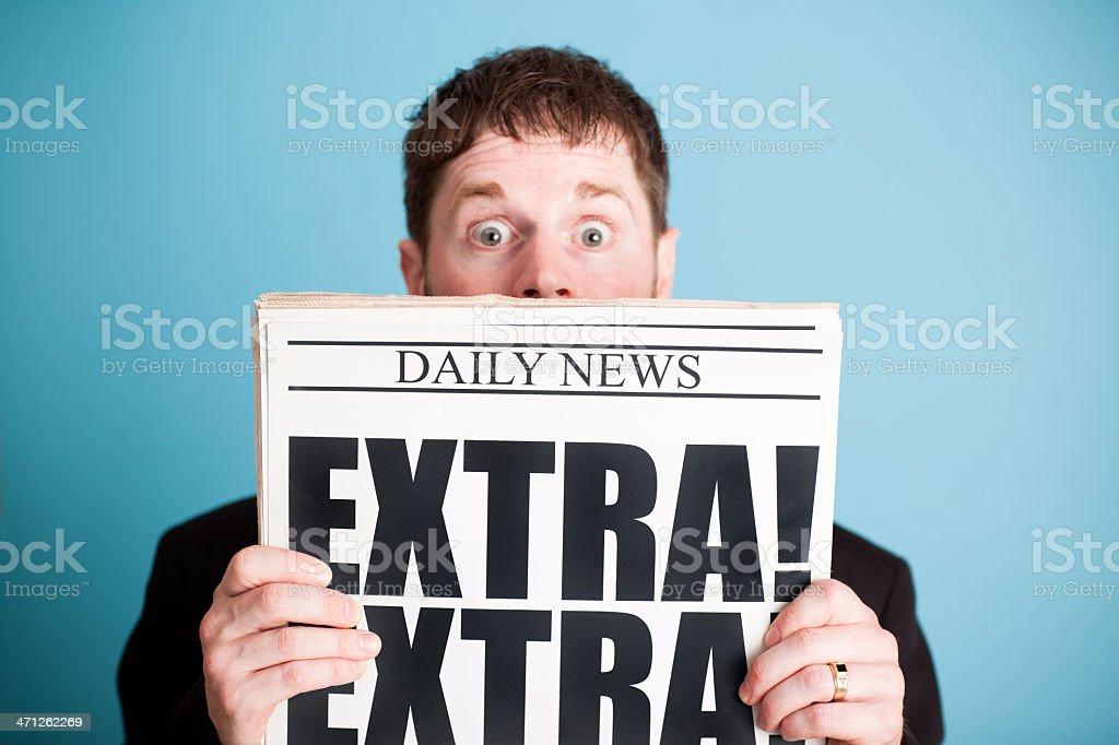 Surprised Businessman Holding Newspaper with Extra! Headline stock photo