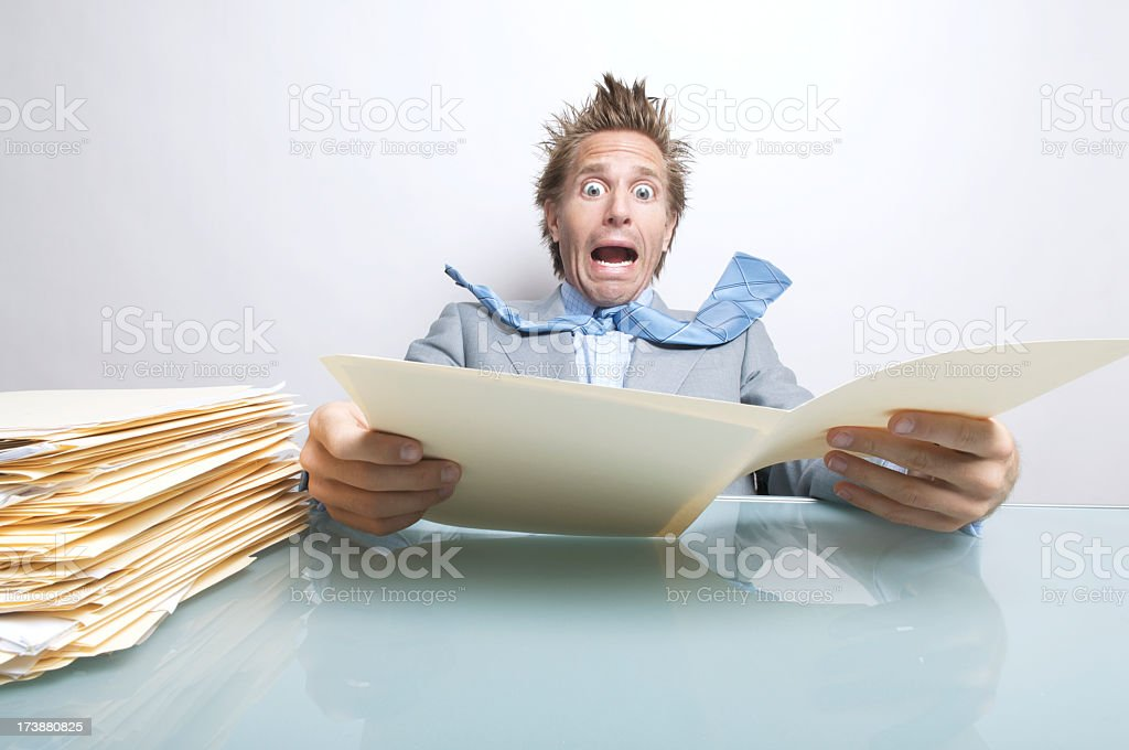 Surprised Businessman Office Worker Opening Stressful File Folder at Desk royalty-free stock photo