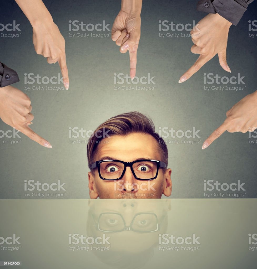 surprised businessman peeking from under the table stock photo