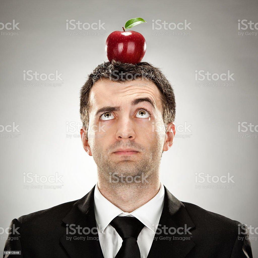 surprised businessman portrait keep red apple on head royalty-free stock photo
