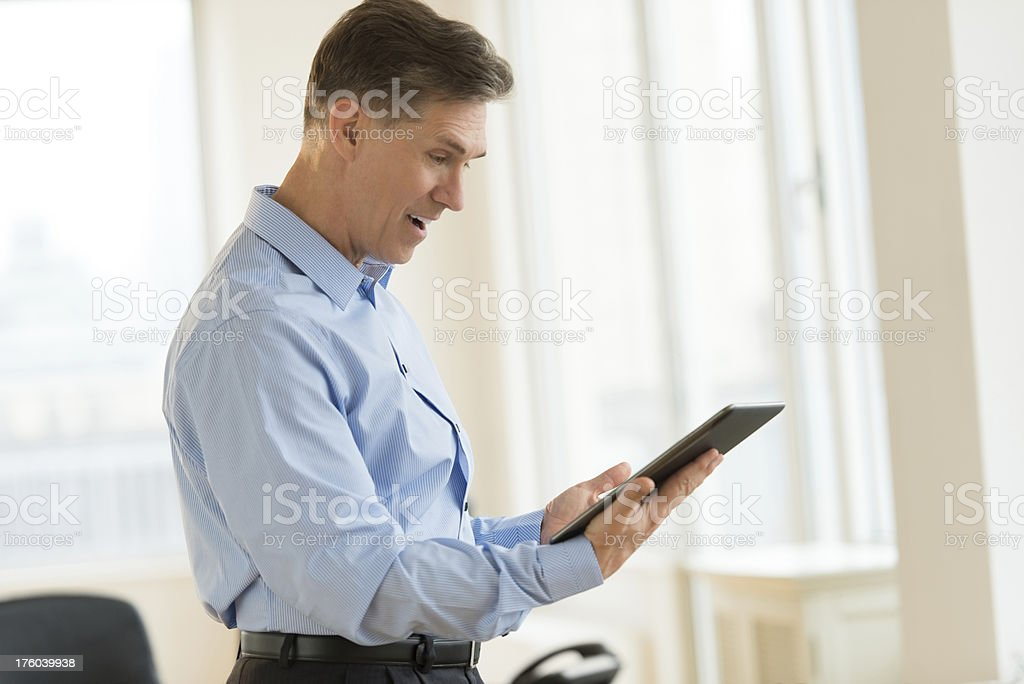Surprised Businessman Using Digital Tablet In Office royalty-free stock photo