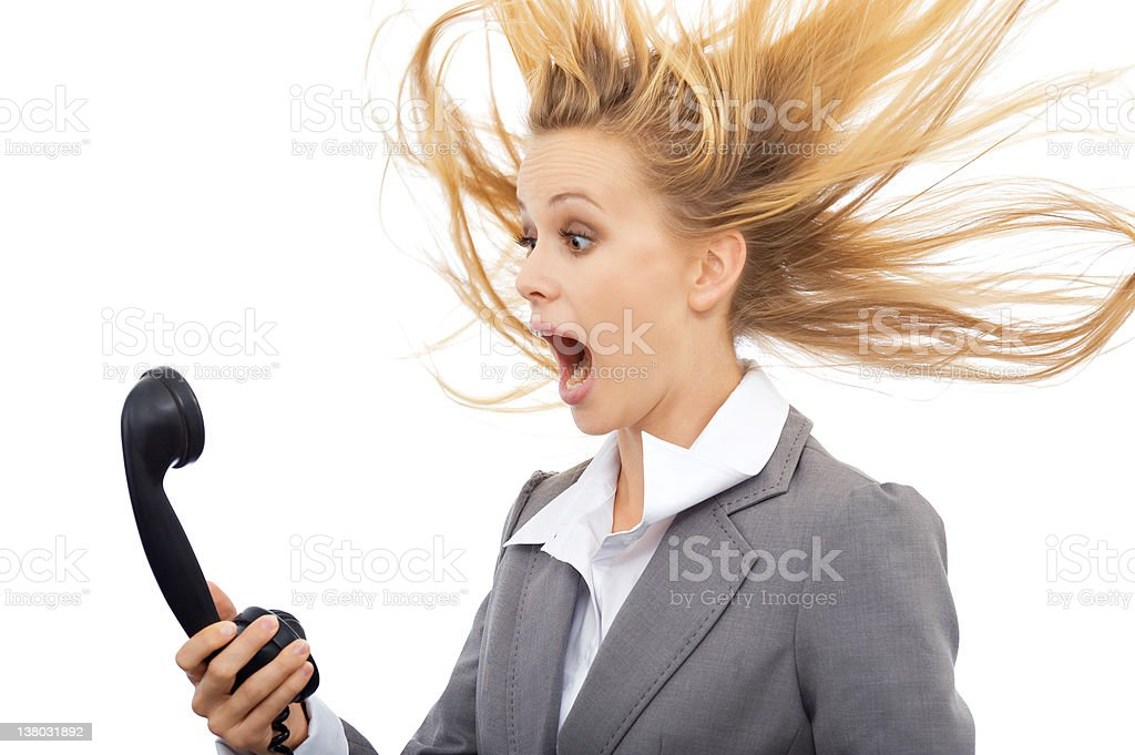 A surprised businesswoman holding a black telephone stock photo