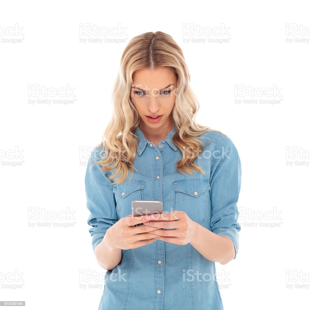 surprised casual blonde woman texting on her smartphone stock photo