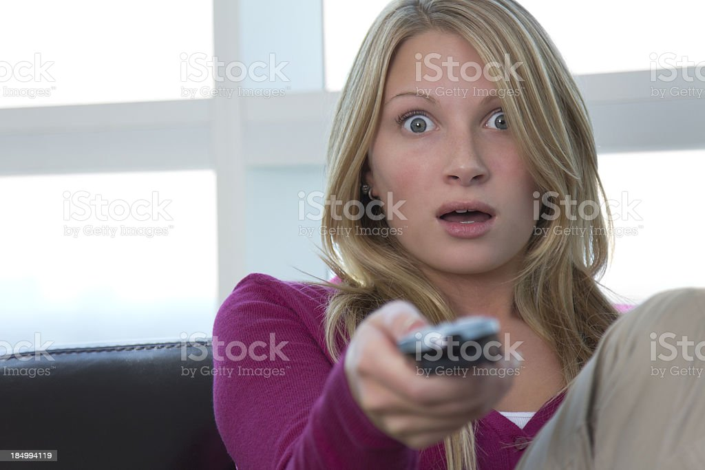 Surprised caucasian female pointing remote control at camera royalty-free stock photo