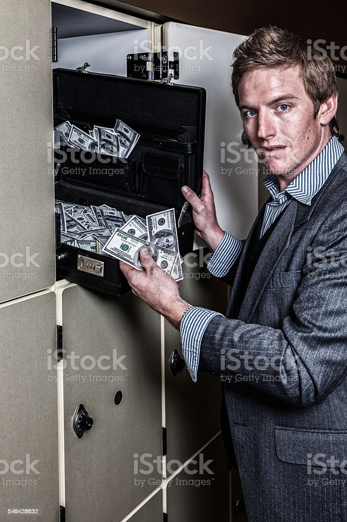 Surprised Confused Young Businessman Discovers Big Money Briefcase stock photo
