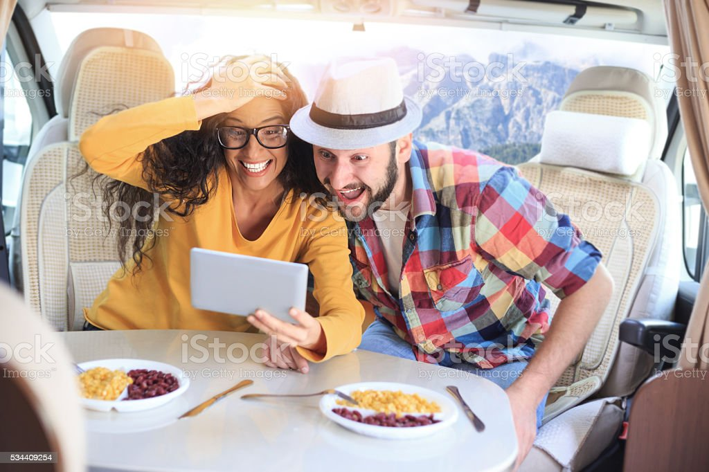 Surprised couple using digital tablet inside of a camper van stock photo