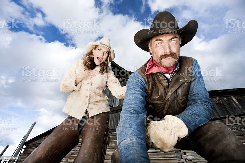 Surprised Cowgirl Watching Cowboy Work stock photo