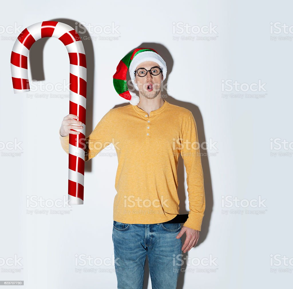 Surprised  Elf with a huge candy cane stock photo