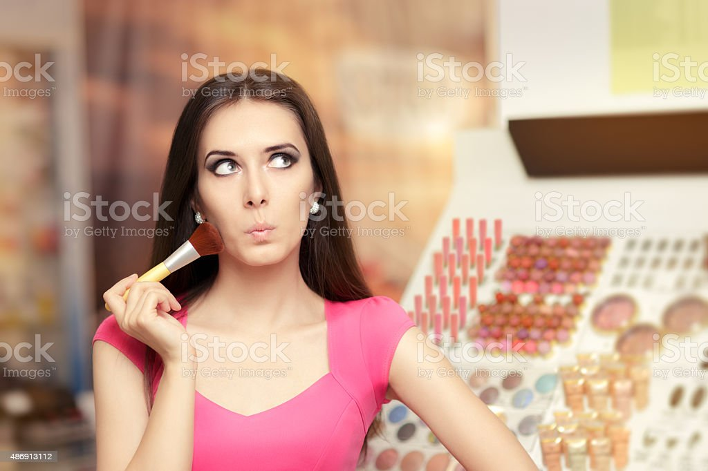 Surprised Girl Holding a Make-up Brush stock photo