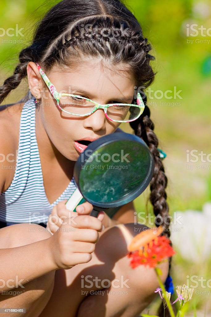 Surprised girl looking through magnifying glass on flower with beetle stock photo