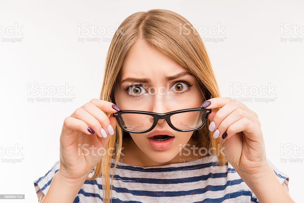 Surprised girl taking off her glasses stock photo