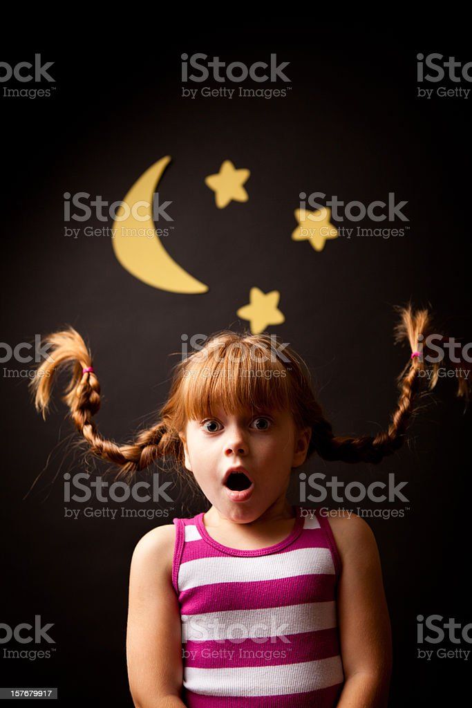 Surprised Girl with Upward Braids Standing Under Moon and Stars stock photo