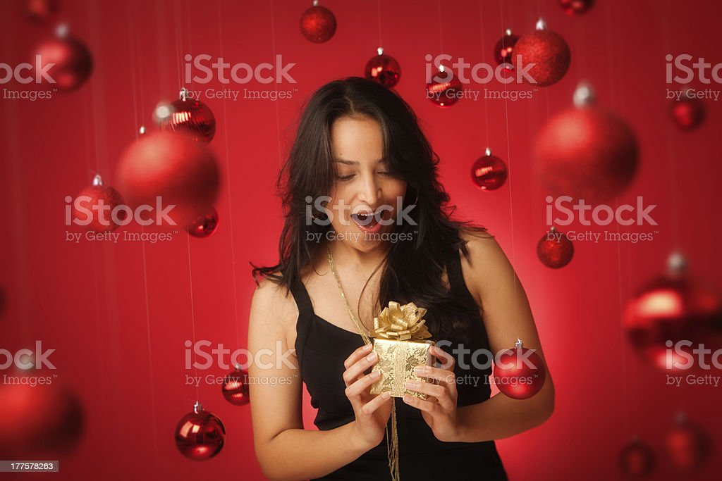 Surprised Hispanic Model in Black Dress Holding Christmas Present Hz royalty-free stock photo