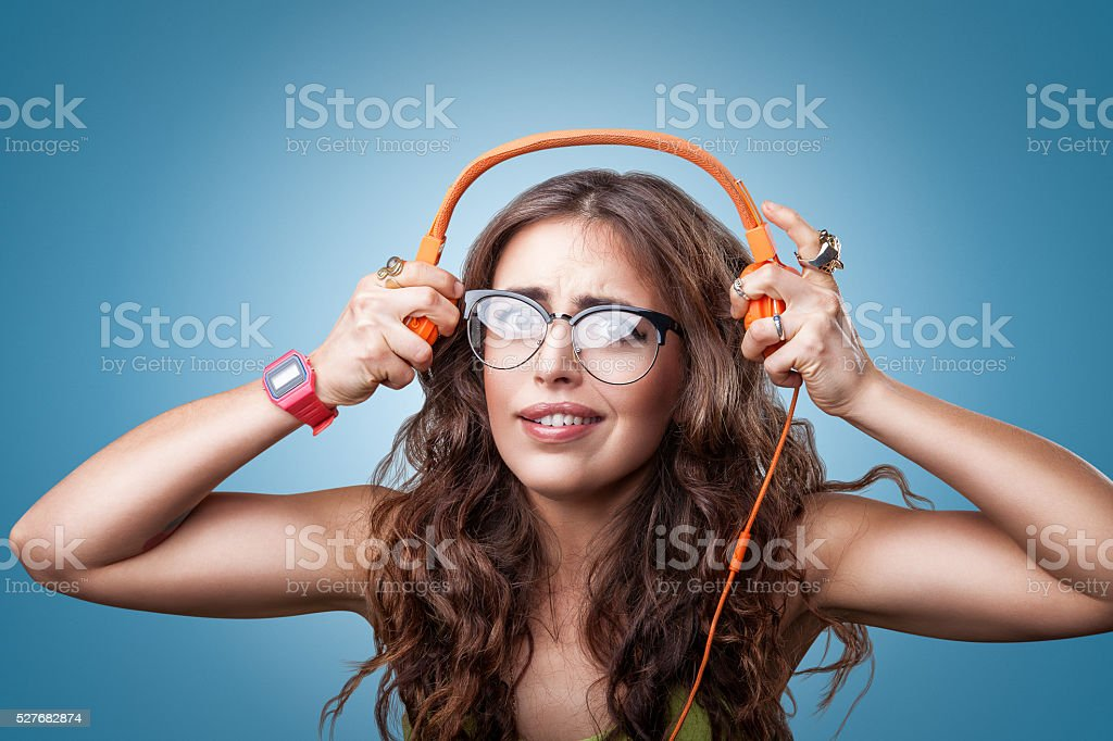 Surprised impressed girl in headphones listening to music. stock photo