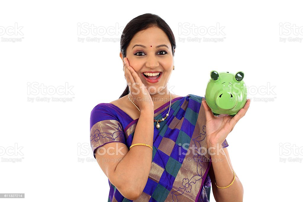 Surprised Indian woman holding piggy bank stock photo
