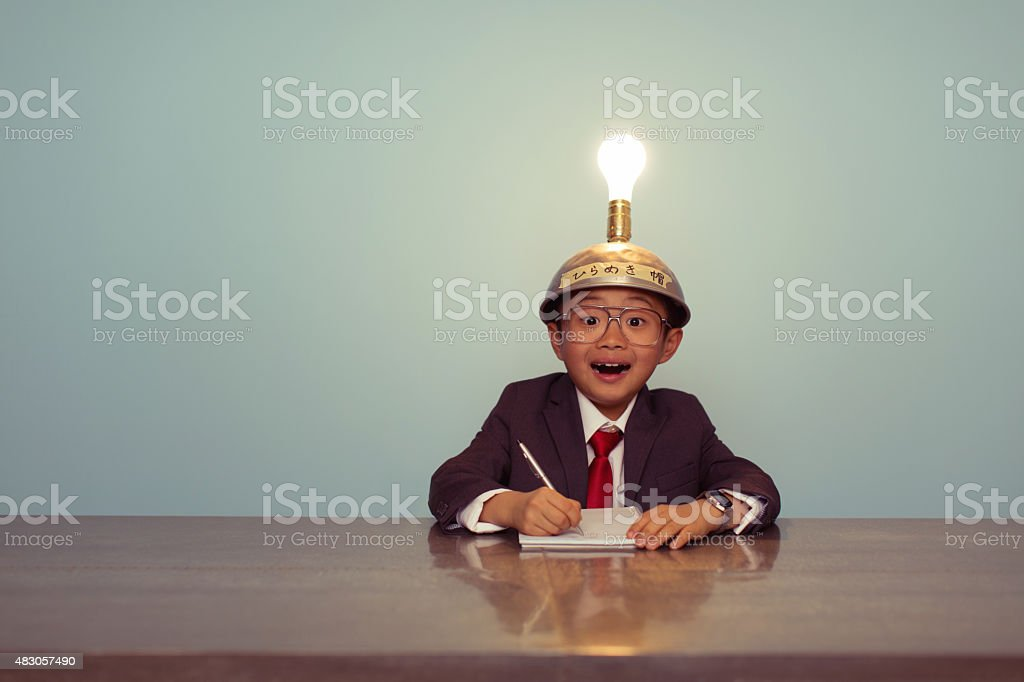 Surprised Japanese Business Boy Wearing Lit Up Thinking Cap stock photo