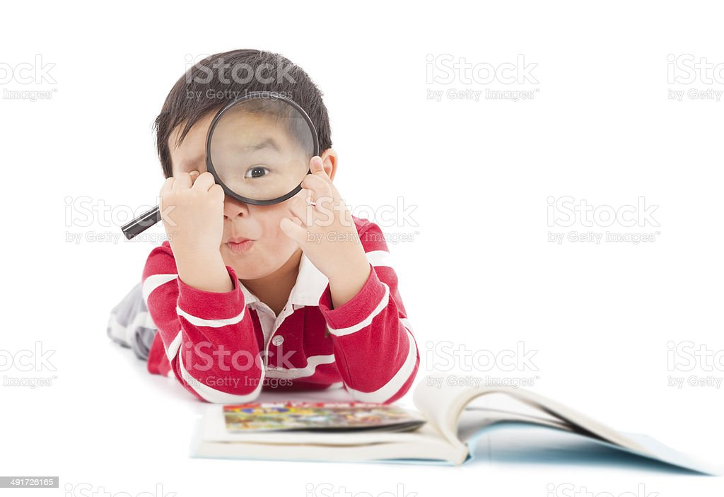 surprised kid looking through from magnifying glass stock photo