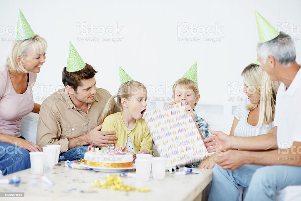Surprised kids opening birthday gift given by his family royalty-free stock photo
