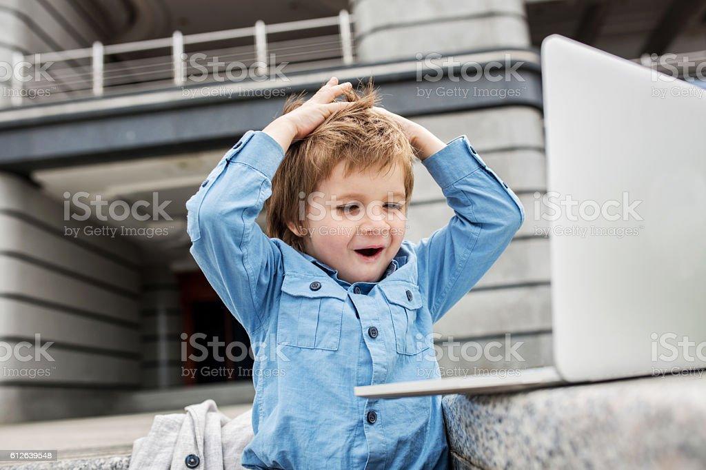 Surprised little boy watching something on laptop. stock photo
