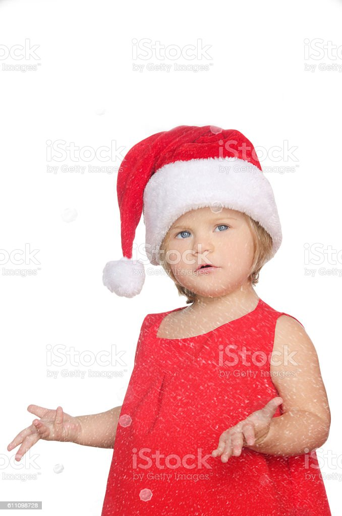surprised little girl in christmas cap, snow stock photo