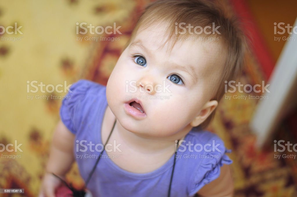 Surprised little girl looking up stock photo