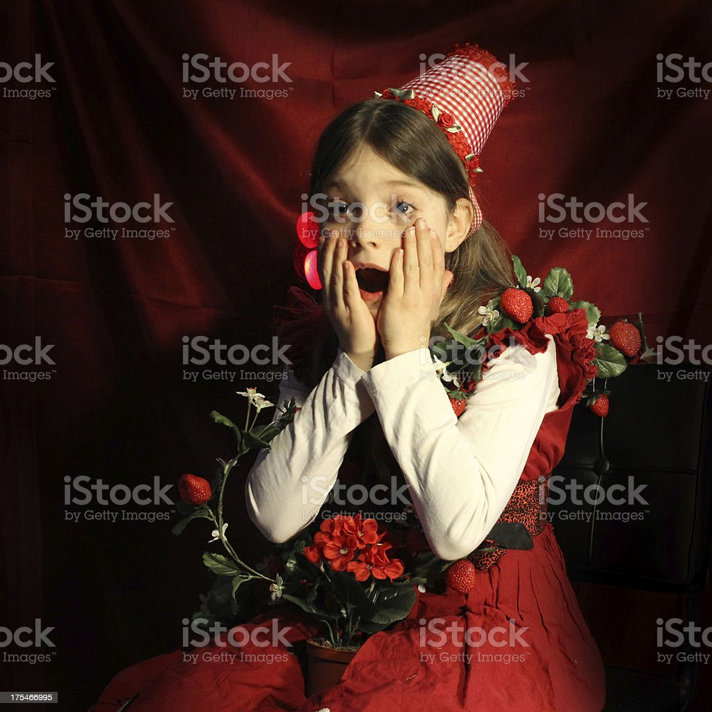 Surprised little girl with flowers and strawberries royalty-free stock photo