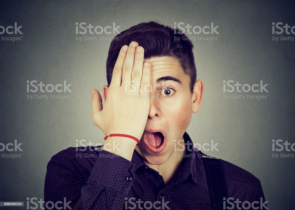 Surprised man covering his eye with hand stock photo