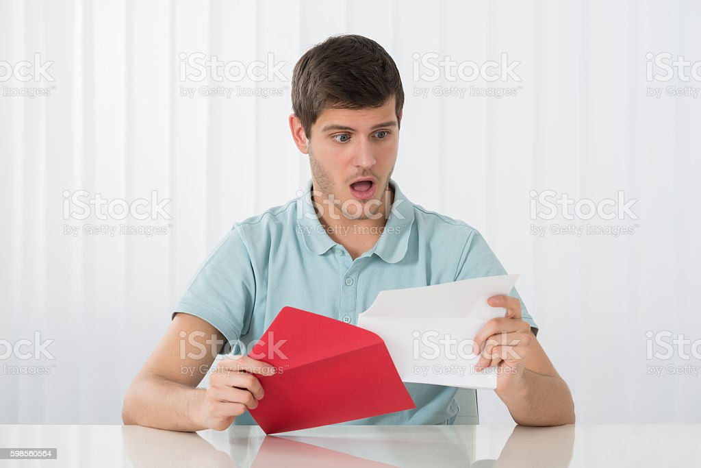 Surprised Man Looking At Letter stock photo