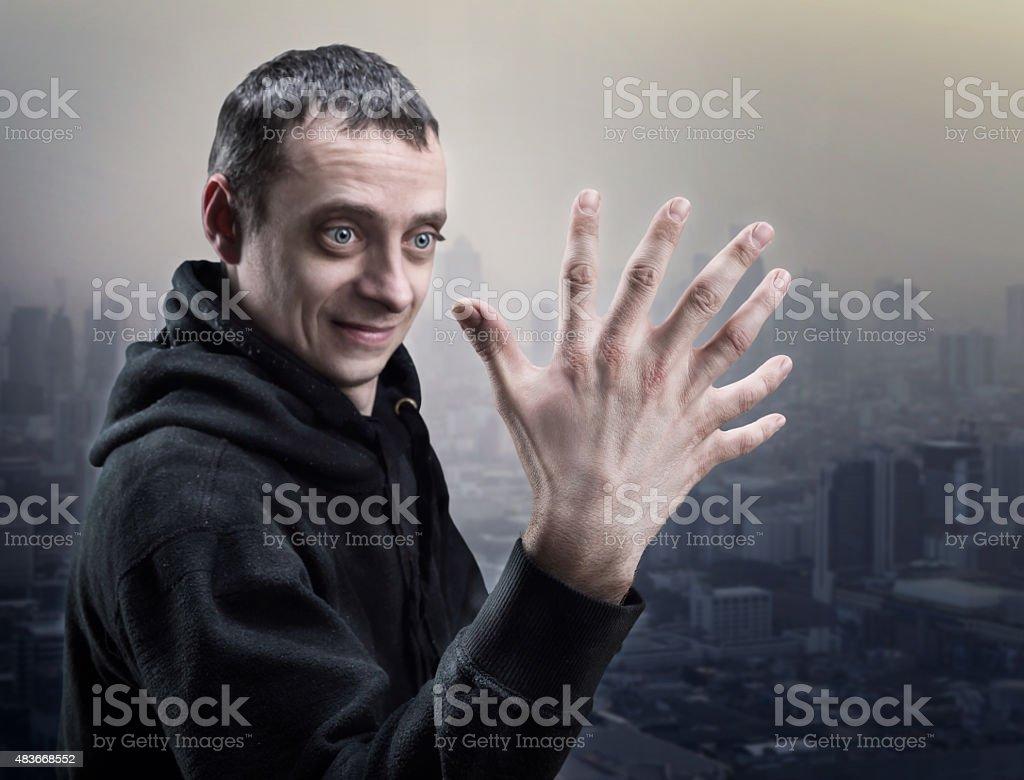 Surprised man looks at his strange hand stock photo