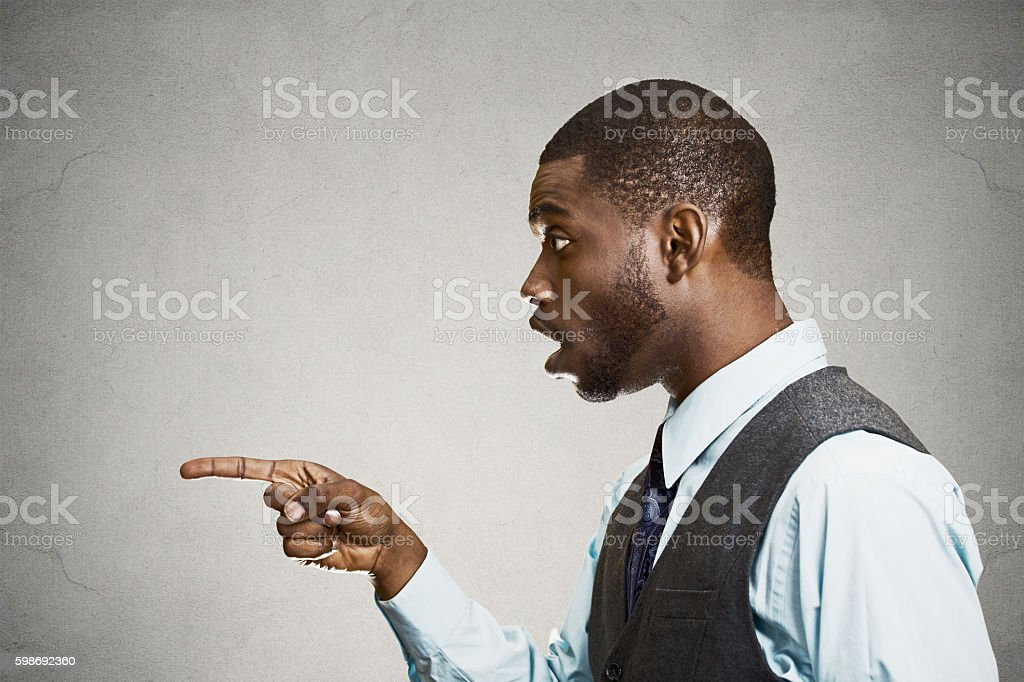 Surprised man pointing with finger at someone stock photo