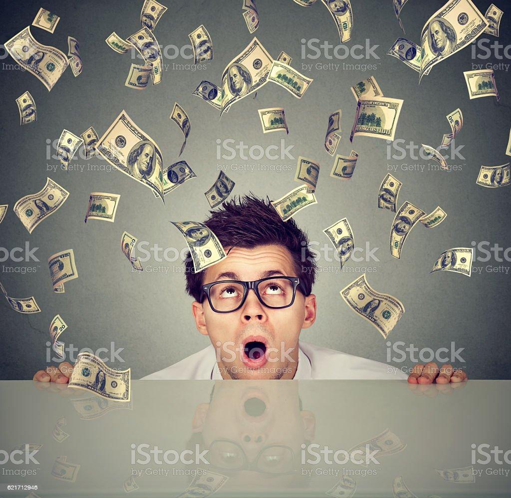 Surprised man under money rain peeking from under table stock photo