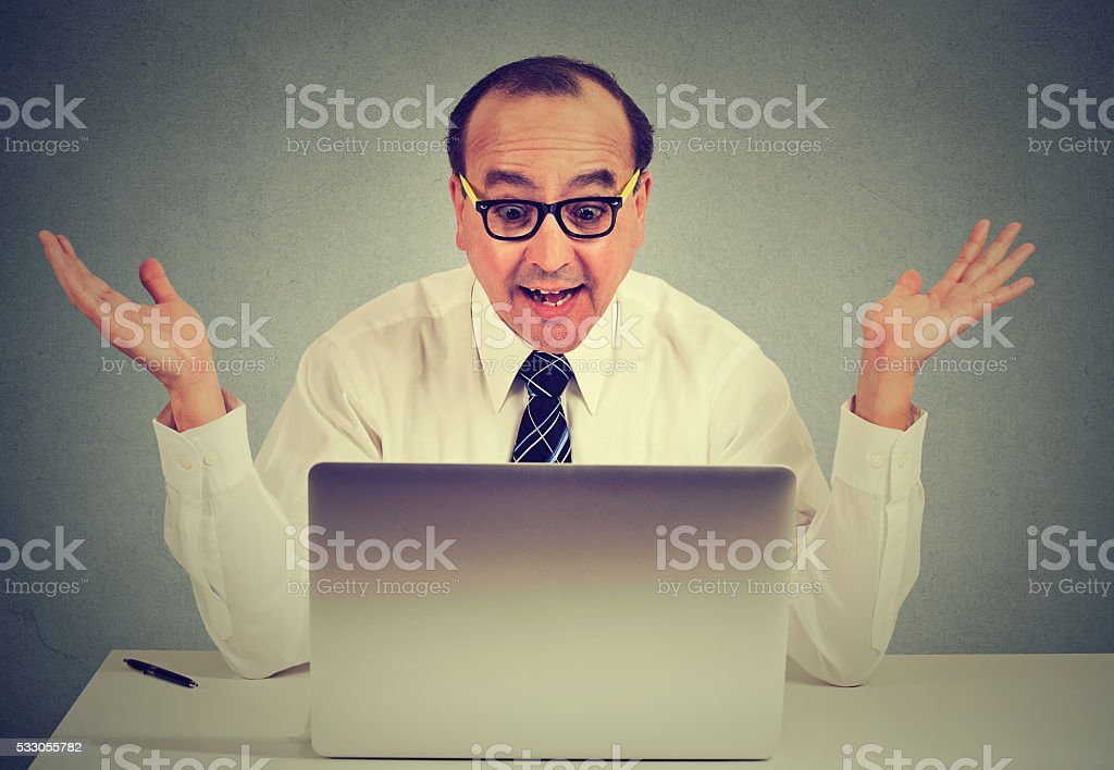 surprised man using a computer in his office stock photo