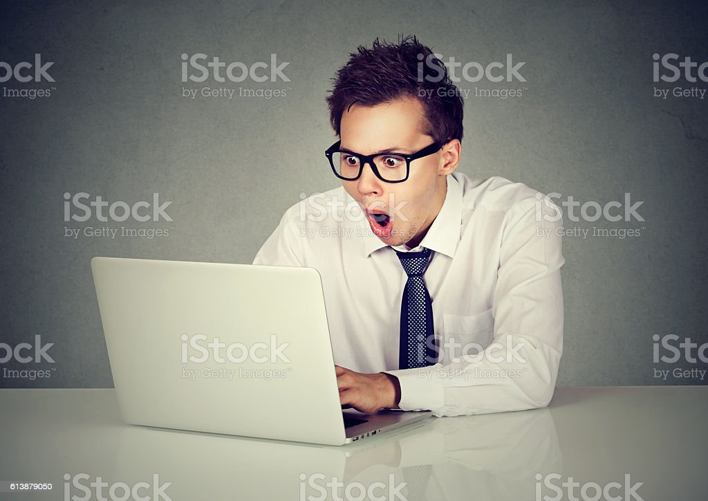 Surprised man using a laptop computer stock photo