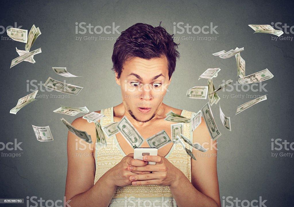 surprised man using smartphone dollar bills flying away from screen stock photo