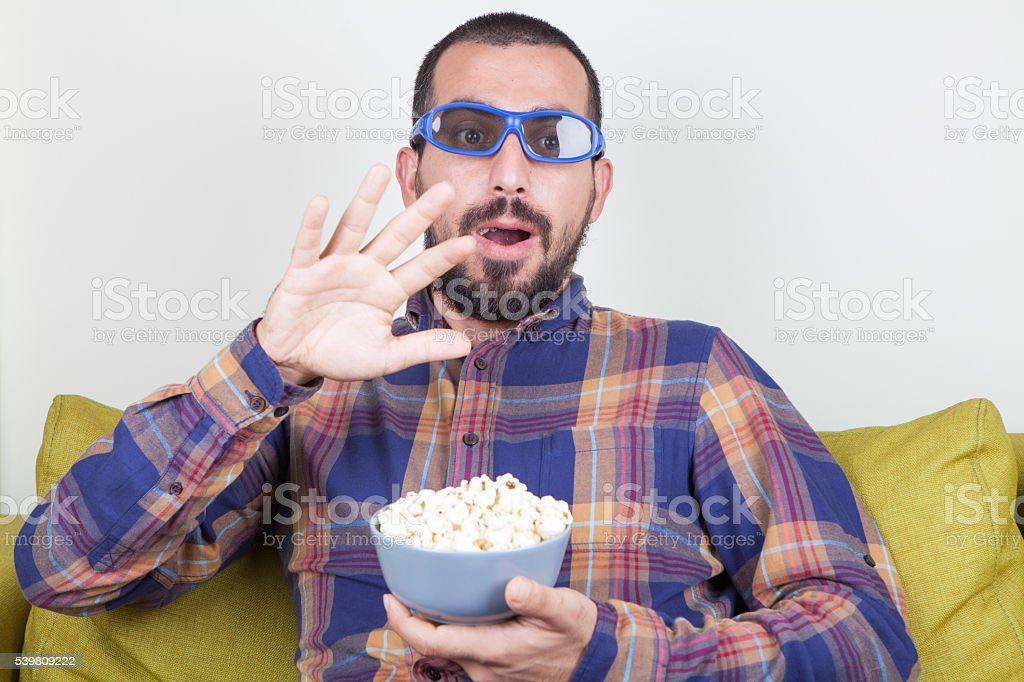Surprised Man Watching A Scary Movie stock photo