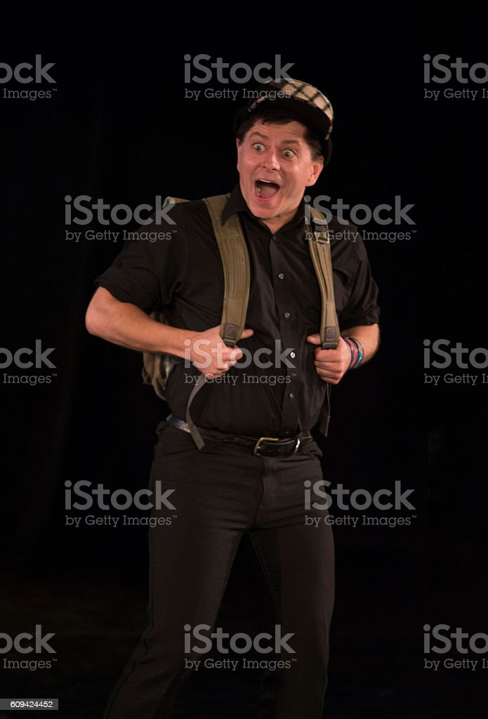 surprised man with backpack walking stock photo